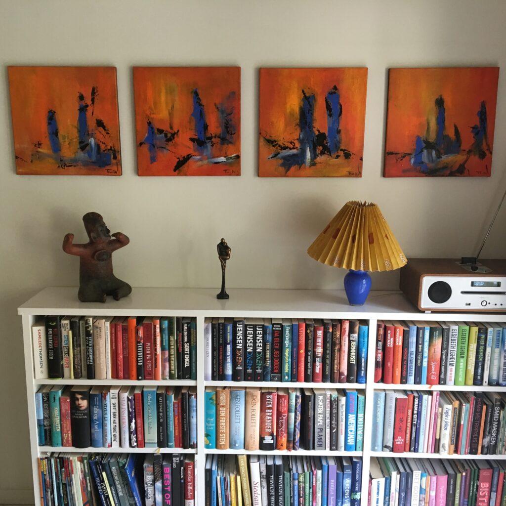 Abstrakte malerier hænger i gruppe over reolen