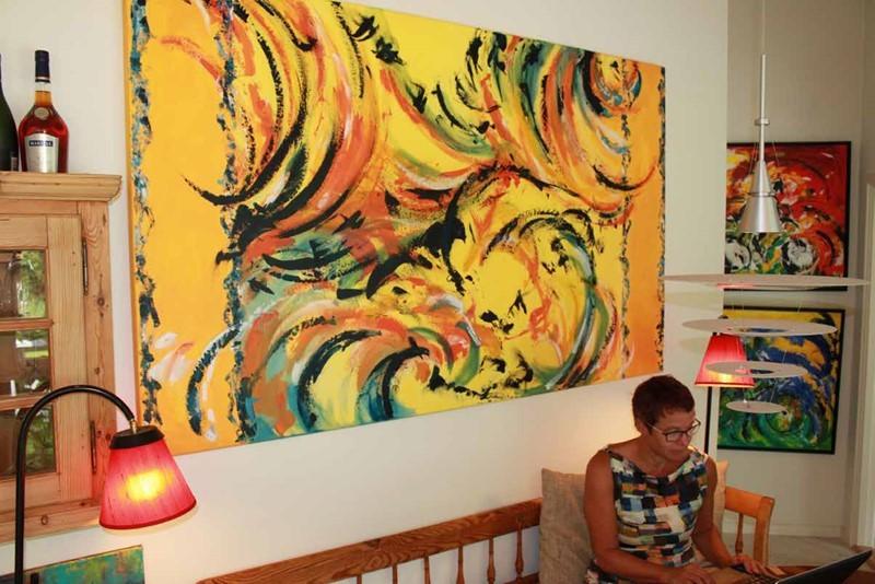 Stort abstrakt maleri bag spisebordet med masser af farver og dynamik